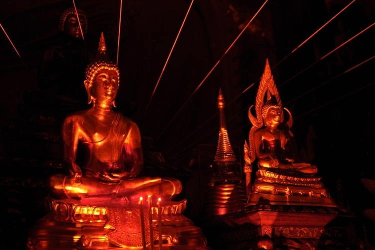 A photo of Buddha images, candlelight, and energy strings.